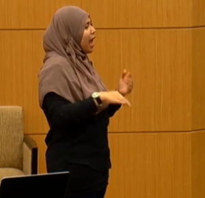 A sign language interpreter translating for conference attendees.