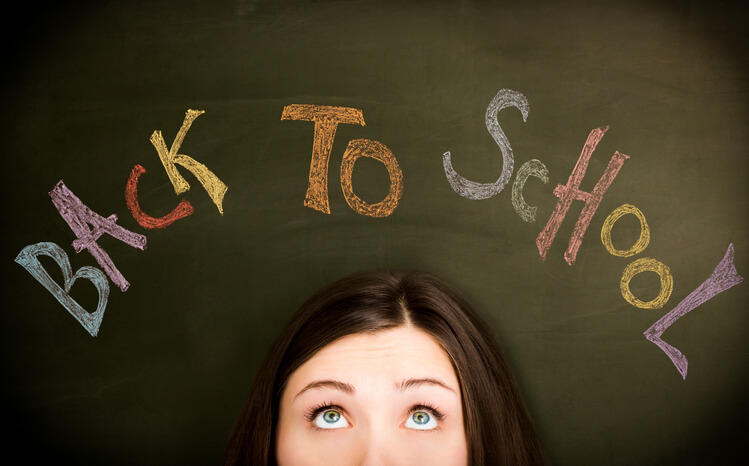 """Young woman in front of """"Back to school"""" concept on blackboard."""
