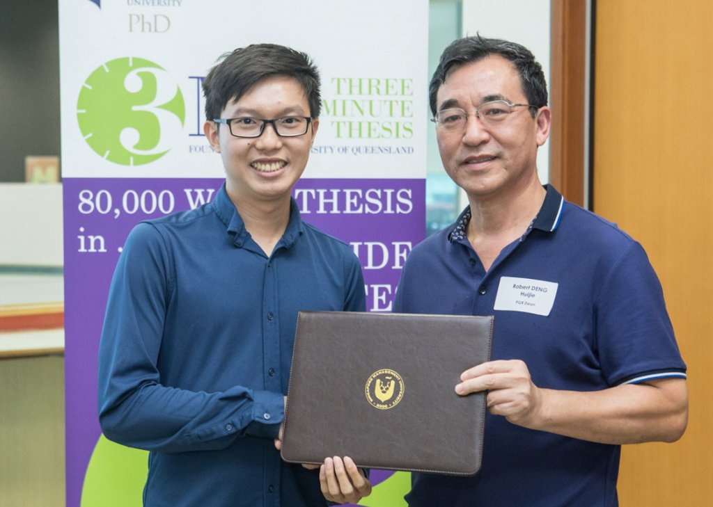 Andree receiving the SMU Presidential Doctoral Fellowship from Professor Robert Deng, SMU's Dean of Postgraduate Research Programmes.