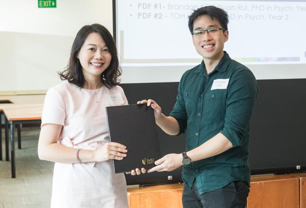 Brandon receiving his SMU Presidential Doctoral Fellowship award in 2018 from SMU Associate Professor Angela Leung