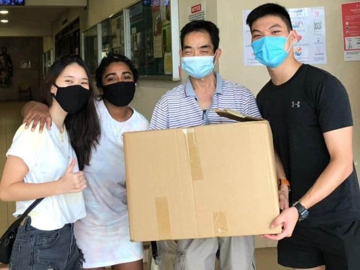 Kenneth (far right), together with his friends, delivering fresh meals to a very grateful caretaker of one of the homeless shelters